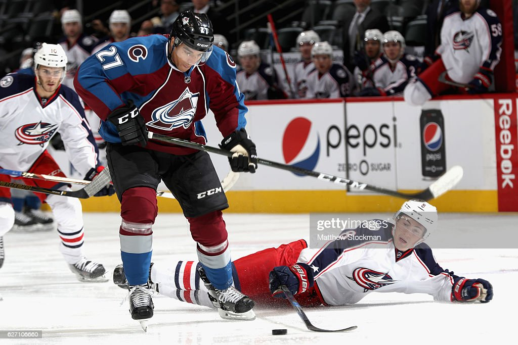 Andreas Martinsen #27 of the Colorado Avalanche takes the puck from Zach Werenski #8 of the Columbus Blue Jackets at the Pepsi Center on December 1, 2016 in Denver, Colorado.