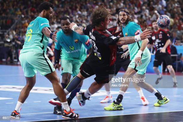 Andreas Nilsson of Veszprem tries to score with a backhand shot against Timothey N'Guessan Cedric Sorhaindo and Viran Morros de Argila of Barcelona...