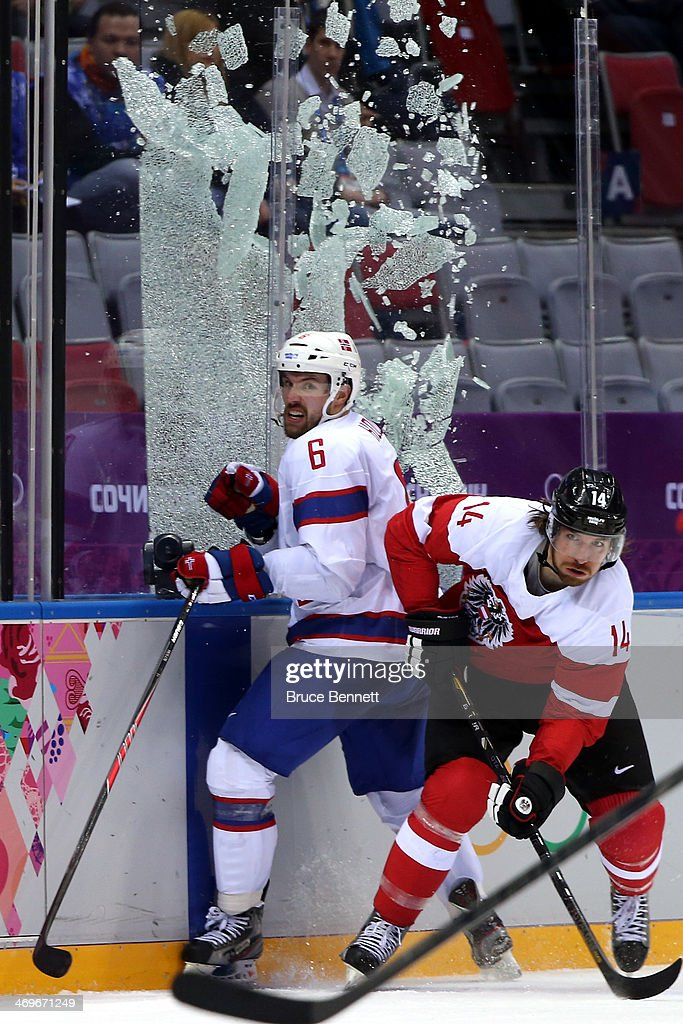 Andreas Nodl #14 of Austria checks Jonas Holos #6 of Norway to break the glass during the Men's Ice Hockey Preliminary Round Group B game on day nine of the Sochi 2014 Winter Olympics at Bolshoy Ice Dome on February 16, 2014 in Sochi, Russia.