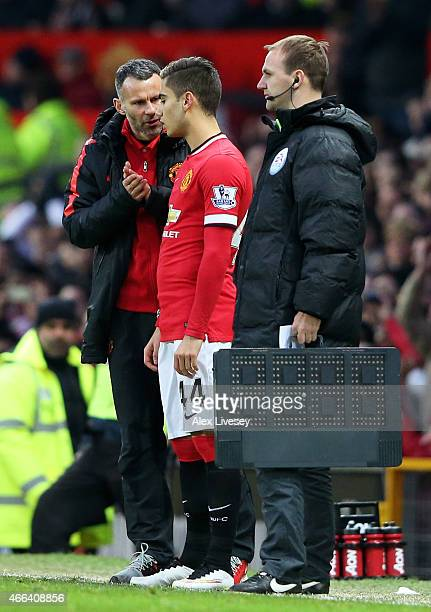 Andreas Pereira of Manchester United receives instructions from Ryan Giggs the assistant manager of Manchester United prior to coming on as a second...