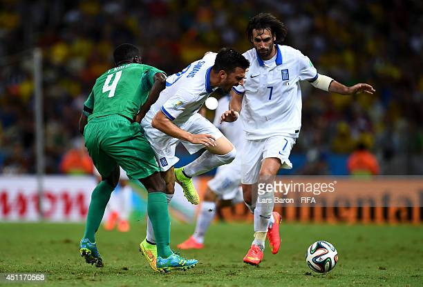 Andreas Samaris of Greece and Kolo Toure of the Ivory Coast compete for the ball during the 2014 FIFA World Cup Brazil Group C match between Greece...