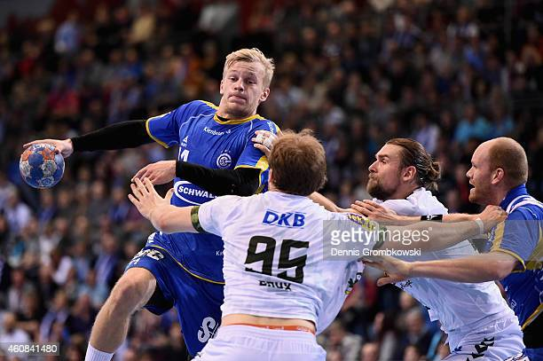 Andreas Schroeder of VfL Gummersbach throws the ball under the pressure of Paul Drux of Fuechse Berlin during the DKB Handball Bundesliga match...