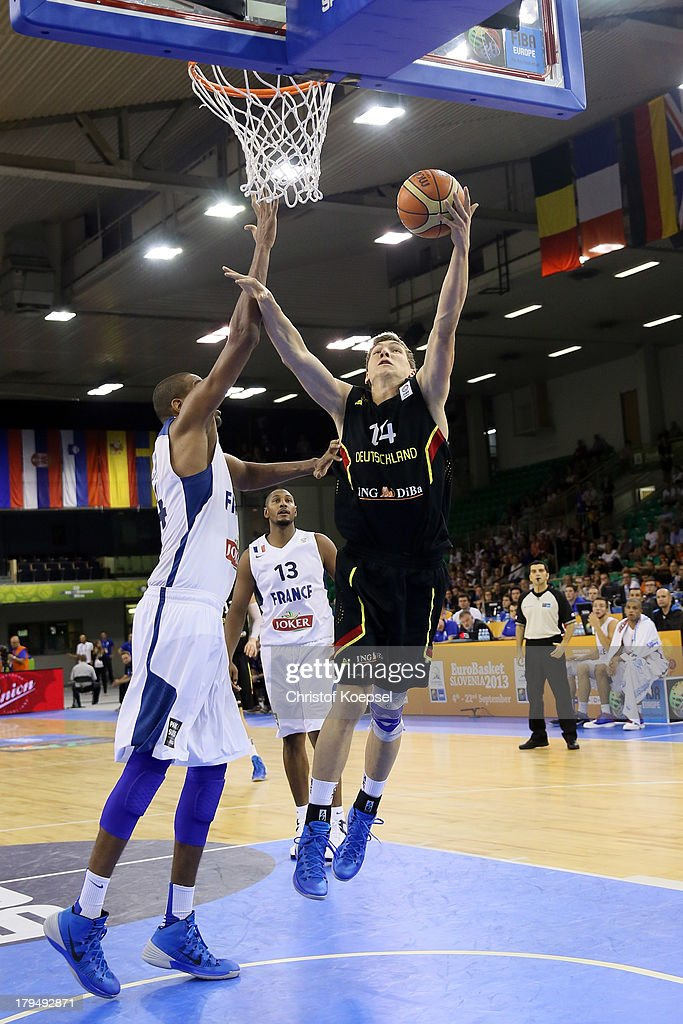 Andreas Seiferth of Gemany (R) shoots over Alexis Ajinca of France (L) during the FIBA European Championships 2013 first round group A match between France and Germany at Tivoli Arena on September 4, 2013 in Ljubljana, Slovenia.