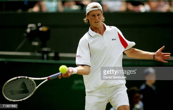 Andreas Seppi of Italy returns a shot to Andre Agassi of the United States during day four of the Wimbledon Lawn Tennis Championships at the All...