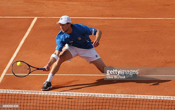 Andreas Seppi of Italy slides to play a forehand volley during the fifth and decisive rubber against James Ward of Great Britain during day three of...