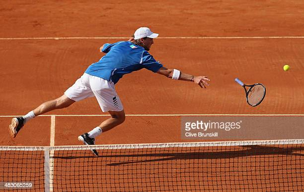 Andreas Seppi of Italy throws his racket to the ball after missing a backhand volley during the fifth and decisive rubber against James Ward of Great...