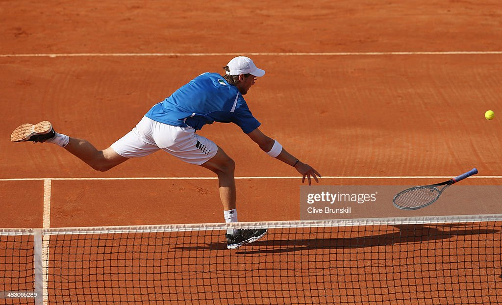 <a gi-track='captionPersonalityLinkClicked' href=/galleries/search?phrase=Andreas+Seppi&family=editorial&specificpeople=228727 ng-click='$event.stopPropagation()'>Andreas Seppi</a> of Italy throws his racket to the ball after missing a backhand volley during the fifth and decisive rubber against James Ward of Great Britain during day three of the Davis Cup World Group Quarter Final match between Italy and Great Britain at Tennis Club Napoli on April 6, 2014 in Naples, Italy.