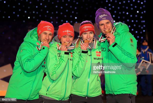 Andreas Wellinger Markus Eisenbichler Svenja Wuerth and Carina Vogt of Germany celebrate with their gold medals after victory in the Mixed Team HS100...
