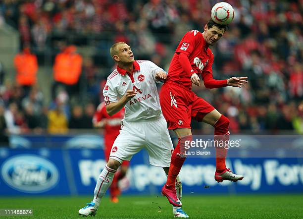 Andreas Wolf of Nuernberg challenges Milivoje Novakovic of Koeln during the Bundesliga match between 1 FC Koeln and 1 FC Nuernberg at...
