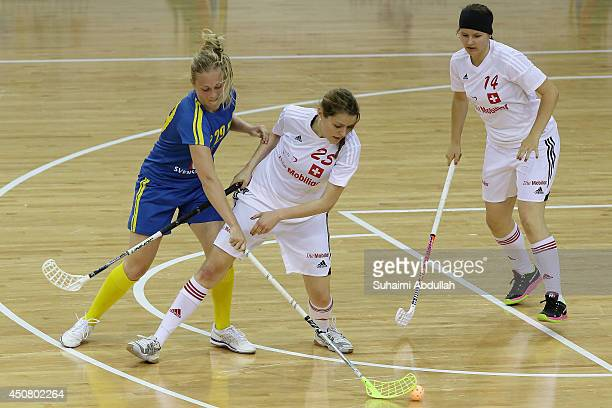 Andreasson Malin of Sweden and Andrea Ressnig of Switzerland challenge for the ball during the World University Championship Floorball match between...