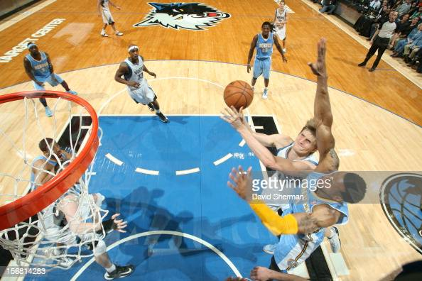 Andrei Kirilenko of the Minnesota Timberwolves goes to the basket against Andre Iguodala of the Denver Nuggets during the game between the Minnesota...