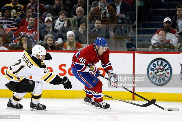 Andrei Kostitsyn of the Montreal Canadiens skates with the puck while being defended by Andrew Ference of the Boston Bruins during the NHL game at...