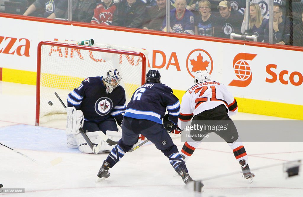Andrei Loktionov #21 of the New Jersey Devils shoots the puck past goaltender Ondrej Pavelec #31 of the Winnipeg Jets for a second period goal at the MTS Centre on February 28, 2013 in Winnipeg, Manitoba, Canada.