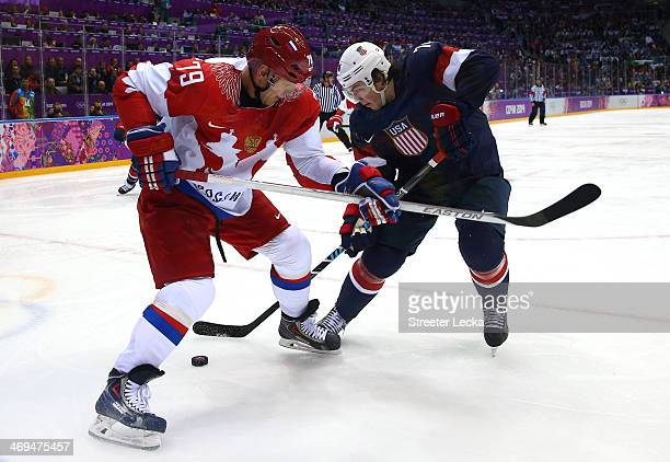 Andrei Markov of Russia and TJ Oshie of the United States fight for the puck during the Men's Ice Hockey Preliminary Round Group A game on day eight...