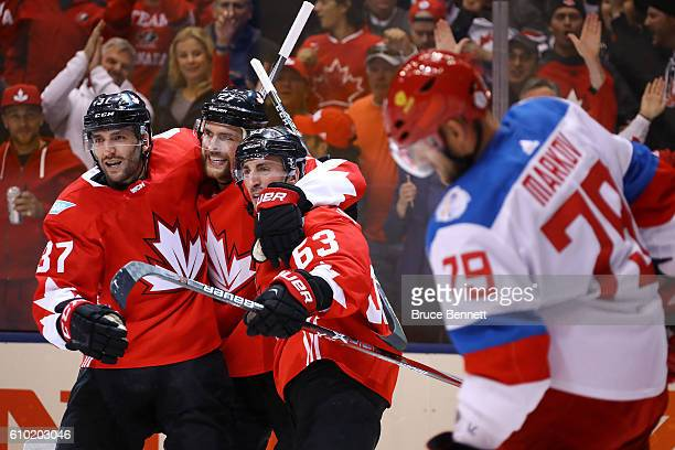 Andrei Markov of Team Russia skates away as Brad Marchand of Team Canada is congratulated by his teammates Patrice Bergeron and Alex Pietrangelo...