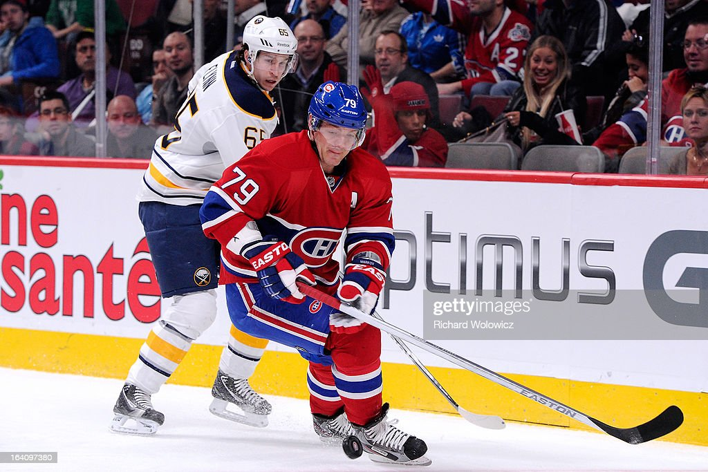 Andrei Markov #79 of the Montreal Canadiens and Brian Flynn #65 of the Buffalo Sabres chase the puck into the corner during the NHL game at the Bell Centre on March 19, 2013 in Montreal, Quebec, Canada.