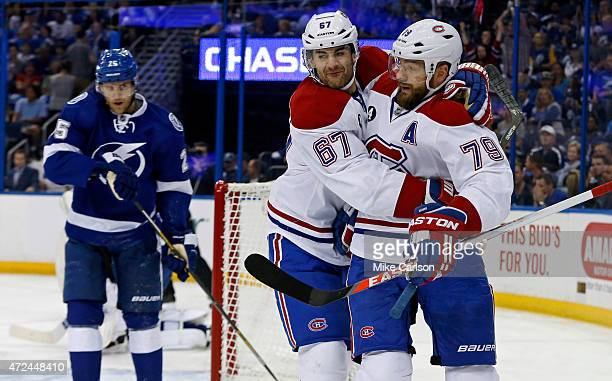 Andrei Markov of the Montreal Canadiens celebrates his goal with Max Pacioretty as Matt Carle of the Tampa Bay Lightning reacts in Game Four of the...
