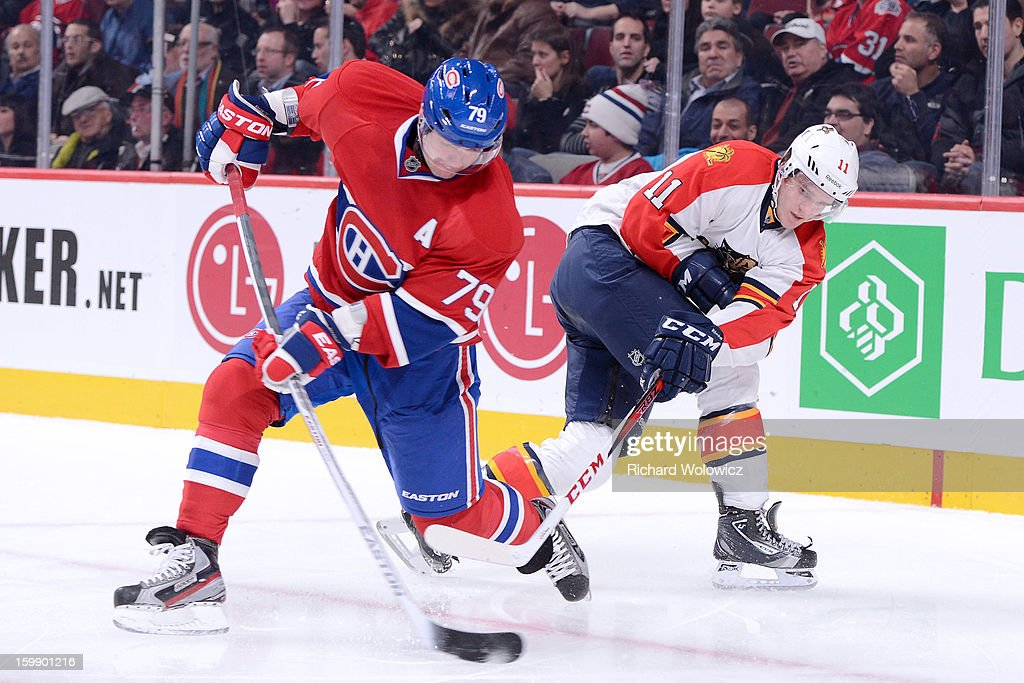 <a gi-track='captionPersonalityLinkClicked' href=/galleries/search?phrase=Andrei+Markov&family=editorial&specificpeople=204528 ng-click='$event.stopPropagation()'>Andrei Markov</a> #79 of the Montreal Canadiens clears the puck in front of <a gi-track='captionPersonalityLinkClicked' href=/galleries/search?phrase=Jonathan+Huberdeau&family=editorial&specificpeople=7144196 ng-click='$event.stopPropagation()'>Jonathan Huberdeau</a> #11 of the Florida Panthers during the NHL game at the Bell Centre on January 22, 2013 in Montreal, Quebec, Canada. The Canadiens defeated the Panthers 4-1.