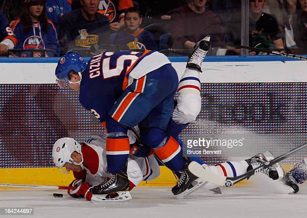 Andrei Markov of the Montreal Canadiens is tripped up by Casey Cizikas of the New York Islanders at the Nassau Veterans Memorial Coliseum on March 21...