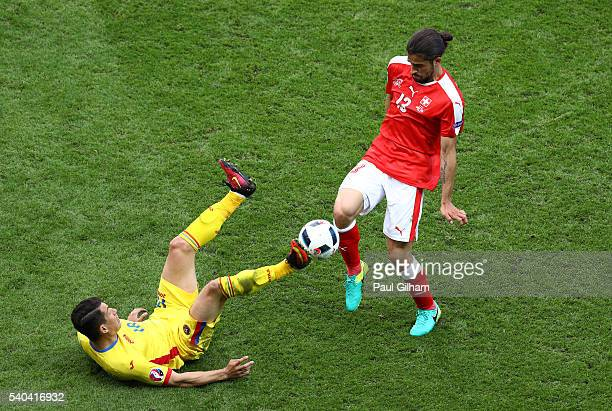 Andrei Prepelita of Romania goes down under a tackle from Ricardo Rodriguez of Switzerland during the UEFA EURO 2016 Group A match between Romania...