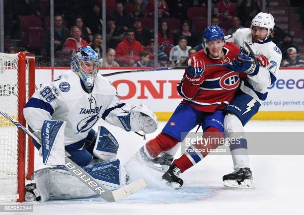 Andrei Vasilevskiy and Victor Hedman of the Tampa Bay Lightning defend the goal against Michael McCarron of the Montreal Canadiens in the NHL game at...