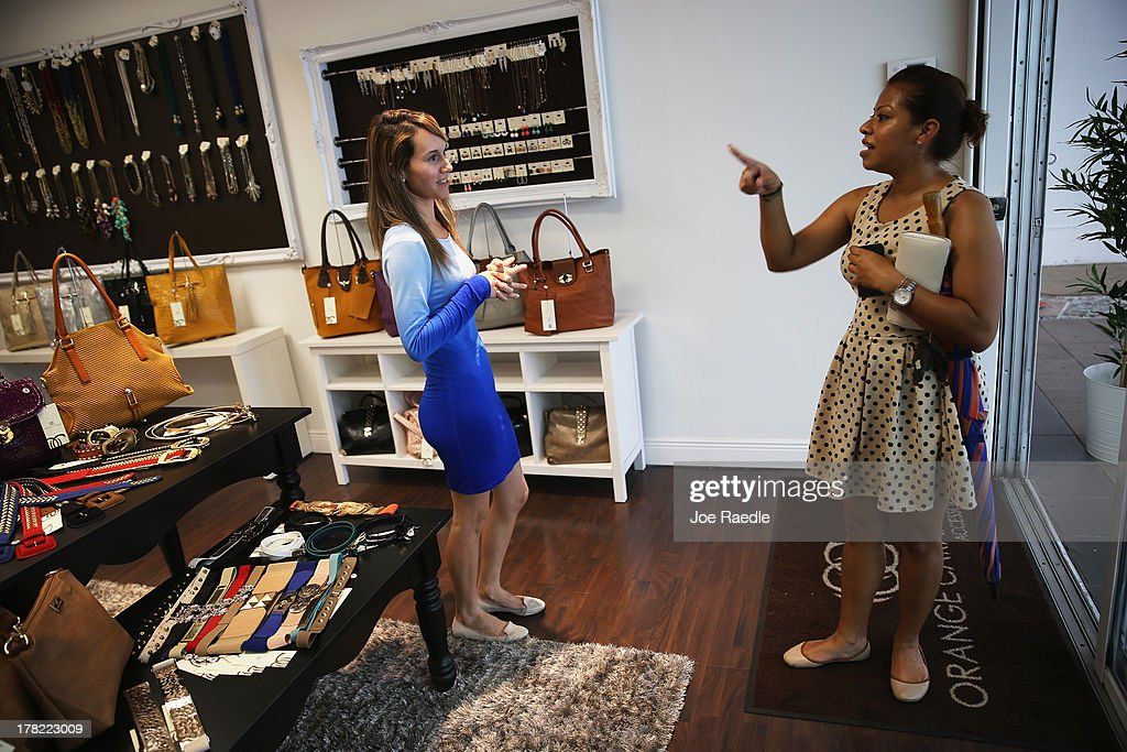 Andreina Flores (L) helps Gabriela Salgado as she shops in her store, Orange Caramelo, on August 27, 2013 in Miami, Florida. The Conference Board announced today that its index of consumer confidence rose to 81.5 this month from a revised 81.0 in July. Some economists reportedly had expected the latest index to edge slightly lower to 79.1.