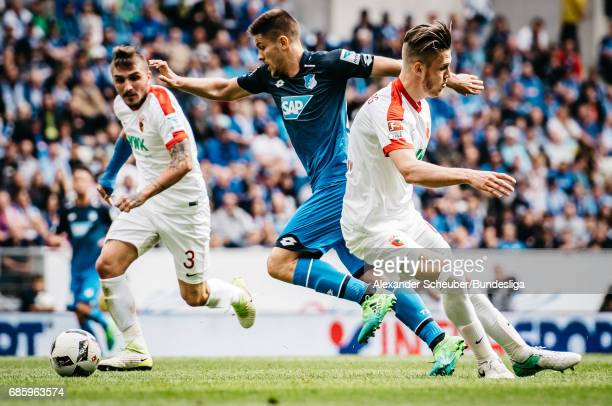 Andrej Kramaric of Hoffenheim in action against Konstantinos Stafylidis of Augsburg and Jeffrey Gouweleeuw of Augsburg during the Bundesliga match...