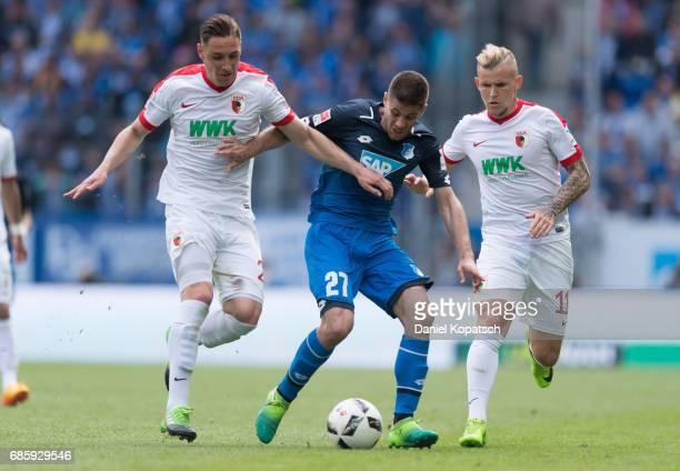 Andrej Kramaric of Hoffenheim is challenged by Dominik Kohr of Augsburg and Jonathan Schmid of Augsburg during the Bundesliga match between TSG 1899...