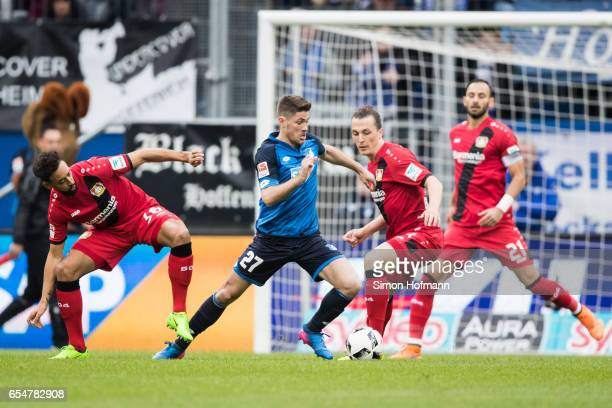 Andrej Kramaric of Hoffenheim is challenged by Julian Baumgartlinger and Karim Bellarabi of Leverkusen during the Bundesliga match between TSG 1899...