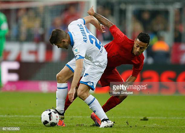 Andrej Kramaric of TSG Hoffenheim is challenged by Thiago Alcantara of FC Bayern Muenchen during the Bundesliga match between Bayern Muenchen and TSG...