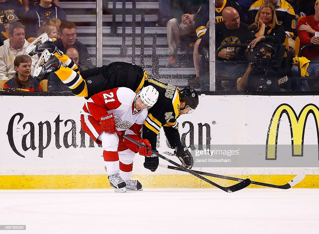 Andrej Meszaros #41 of the Boston Bruins flips over Tomas Tatar #21 of the Detroit Red Wings in the third period during the game at TD Garden on April 20, 2014 in Boston, Massachusetts.