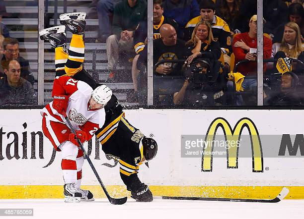 Andrej Meszaros of the Boston Bruins flips over Tomas Tatar of the Detroit Red Wings in the third period during the game at TD Garden on April 20...