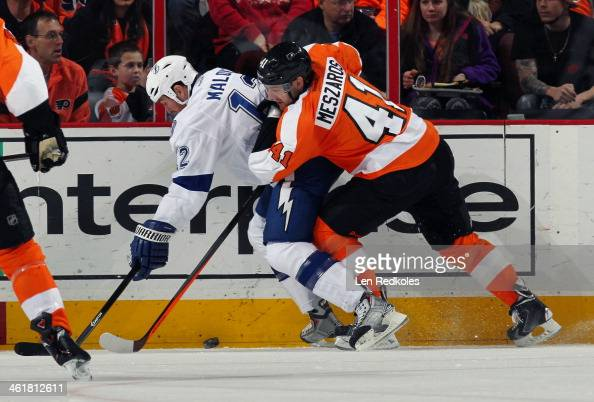 Andrej Meszaros of the Philadelphia Flyers battles for the loose puck along the boards with Ryan Malone of the Tampa Bay Lightning on January 11 2014...