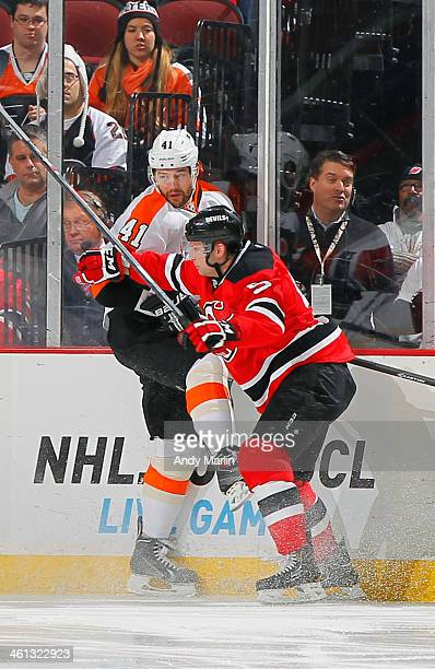 Andrej Meszaros of the Philadelphia Flyers is checked along the boards by Adam Larsson of the New Jersey Devils during the game at the Prudential...