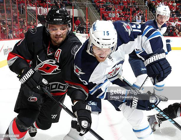Andrej Sekera of the Carolina Hurricanes and Matt Halischuk of the Winnipeg Jets take their battle for the puck into the corner boards during their...