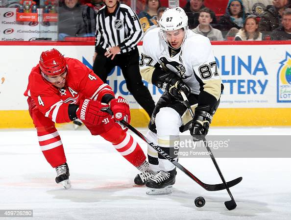Andrej Sekera of the Carolina Hurricanes battes for the puck against Sidney Crosby of the Pittsburgh Penguins during their NHL game at PNC Arena on...