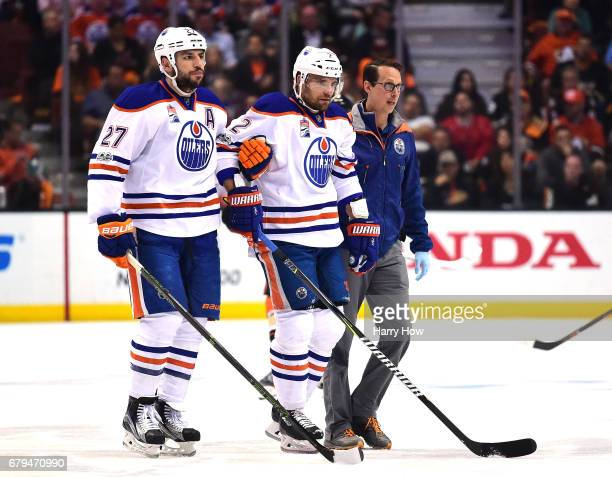 Andrej Sekera of the Edmonton Oilers is helped off the ice by Milan Lucic and a trainer during the first period against the Anaheim Ducks in Game...