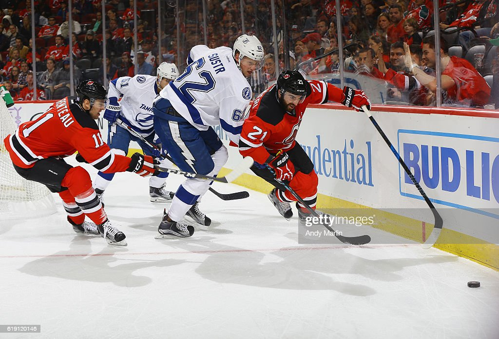 Andrej Sustr #62 of the Tampa Bay Lightning and PA Parenteau #11 and Kyle Palmieri #21 of the New Jersey Devils pursue a poose puck during the game at Prudential Center on October 29, 2016 in Newark, New Jersey.