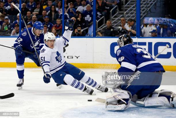 Andrej Sustr of the Tampa Bay Lightning checks Jake Gardiner of the Toronto Maple Leafs in front of goalie Ben Bishop at the Tampa Bay Times Forum on...