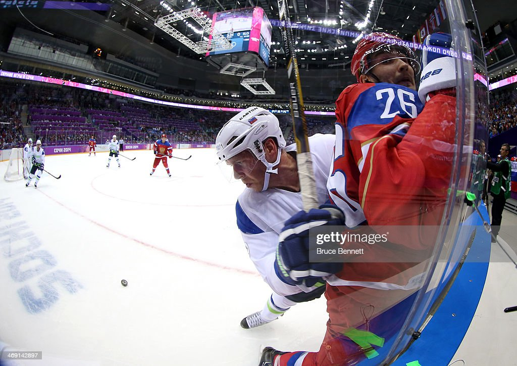 Andrej Tavzelj of Slovenia checks Vyacheslav Voynov of Russia into the glass in the first period during the Men's Ice Hockey Preliminary Round Group...