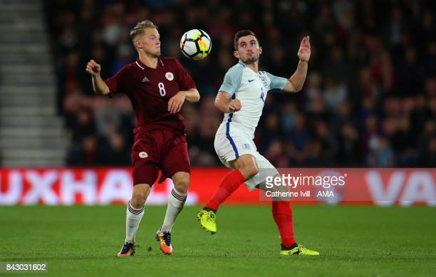 Andrejs Ciganiks of Latvia and Lewis Cook of England during the UEFA Under 21 Championship Qualifier match between England and Latvia at Vitality...