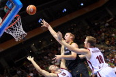 Andrejs Selakovs and Rihards Kuksiks of Latvia defend against Chris Kaman of Germany during the EuroBasket 2011 first round group B match between...