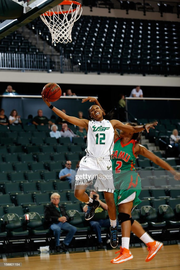 Andrell Smith #12 of the South Florida Bulls drives to the basket as Keturah Martin #2 of the Florida A&M Rattlers fouls her during the game at the Sun Dome on December 29, 2012 in Tampa, Florida.