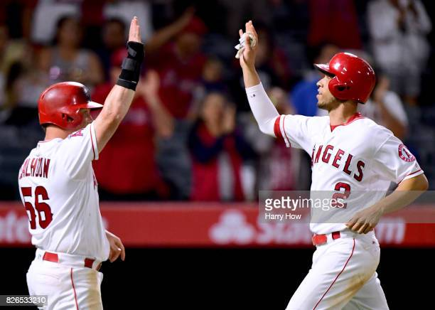 Andrelton Simmons and Kole Calhoun of the Los Angeles Angels celebrate their runs from a Luis Valbuena single to tie the Oakland Athletics 66 during...