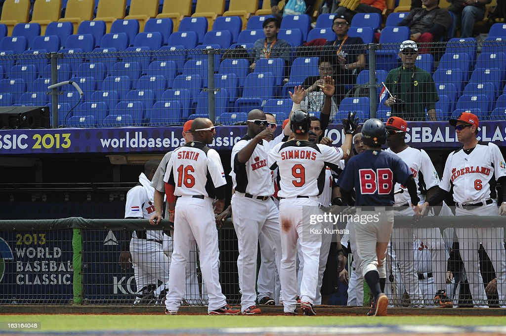 <a gi-track='captionPersonalityLinkClicked' href=/galleries/search?phrase=Andrelton+Simmons&family=editorial&specificpeople=8978424 ng-click='$event.stopPropagation()'>Andrelton Simmons</a> #9 of Team Netherlands is greeted in the dugout by teammates after scoring a run in the bottom of the first inning during Pool B, Game 5 between Team Australia and Team Netherlands during the first round of the 2013 World Baseball Classic at Taichung Intercontinental Baseball Stadium on Tuesday, March 5, 2013 in Taichung, Taiwan.