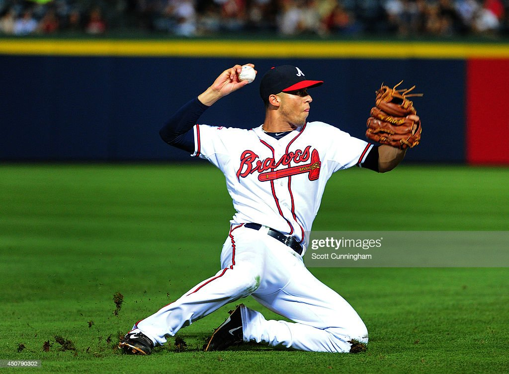 Andrelton Simmons #19 of the Atlanta Braves attempts to throw out a runner at first base during the ninth inning against the Philadelphia Phillies at Turner Field on June 17, 2014 in Atlanta, Georgia.