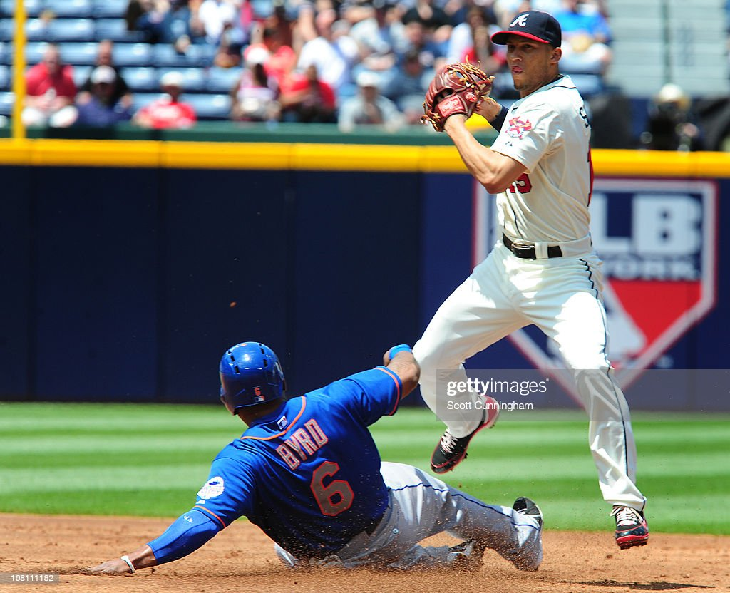 <a gi-track='captionPersonalityLinkClicked' href=/galleries/search?phrase=Andrelton+Simmons&family=editorial&specificpeople=8978424 ng-click='$event.stopPropagation()'>Andrelton Simmons</a> #19 of the Atlanta Braves attempts to turn a double play against <a gi-track='captionPersonalityLinkClicked' href=/galleries/search?phrase=Marlon+Byrd&family=editorial&specificpeople=217377 ng-click='$event.stopPropagation()'>Marlon Byrd</a> #6 of the New York Mets at Turner Field on May 5, 2013 in Atlanta, Georgia.