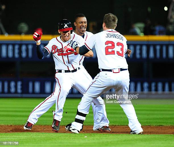 Andrelton Simmons of the Atlanta Braves celebrates with Chris Johnson and B J Upton after knocking in the gamewinning run in the 9th inning against...