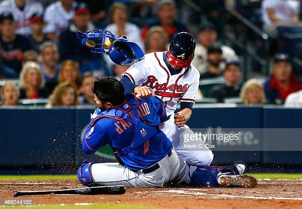 Andrelton Simmons of the Atlanta Braves collides with Travis d'Arnaud of the New York Mets as he is tagged out at homeplate in the second inning...