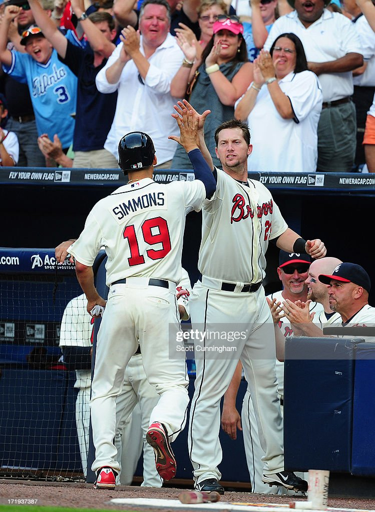 Andrelton Simmons #19 of the Atlanta Braves is congratulated by Chris Johnson #23 after scoring the go-ahead run in the eighth inning against the Arizona Diamondbacks at Turner Field on June 29, 2013 in Atlanta, Georgia.